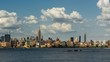 Cityscape time lapse of a summer afternoon in New York City, Manhattan. View of Midtown West skyscrapers, West Village and Hudson River with passing clouds