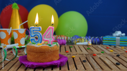 Photo  Birthday cake with candles on rustic wooden table with background of colorful balloons, gifts, plastic cups and candies with blue wall in the background