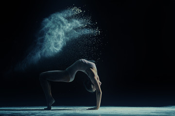 Concept photo. Female dancer in cloud of dust