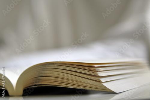 Obraz Otwarta książka na białym stoliku.  - fototapety do salonu