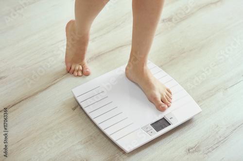 Fotografie, Obraz  Female leg stepping on floor scales