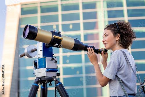 girl looking through a telescope outdoors Canvas Print