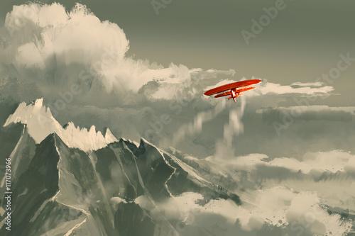 Plakaty czerwony dwupłatowiec lecący nad górami