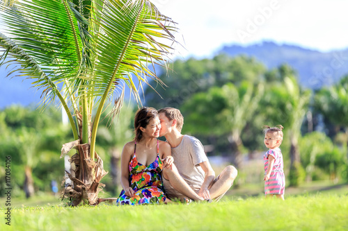 Poster Palmier young family spending time in a tropical garden