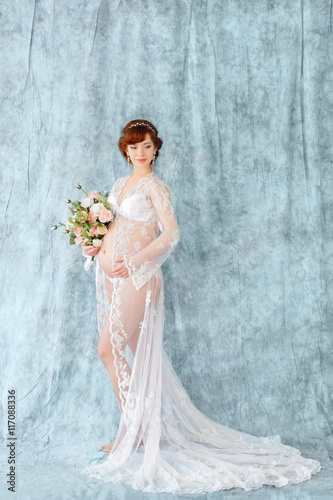 260653af9 Pregnant woman holding flowers, standing in the boudoir dress (negligee) on  a blue background.