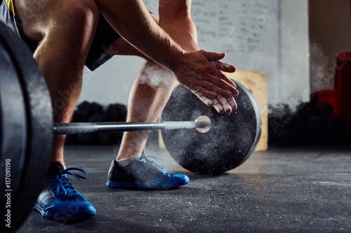 Closeup of weightlifter clapping hands before  barbell workout a Fotobehang
