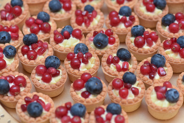 Fototapeta Mini tarts with vanilla cream, blueberries and redcurrants