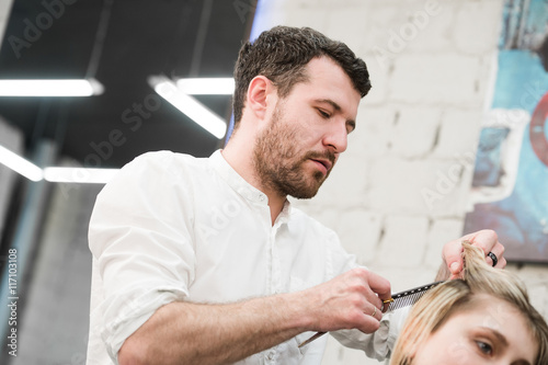 Hairdresser cutting client's hair in salon with electric razor closeup Slika na platnu