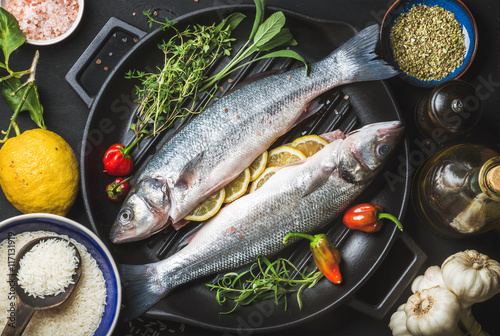 Fotobehang Vis Ingredients for cookig healthy fish dinner. Raw uncooked seabass fish with rice, lemon, herbs and spices on black grilling iron pan over dark background, top view, horizontal composition