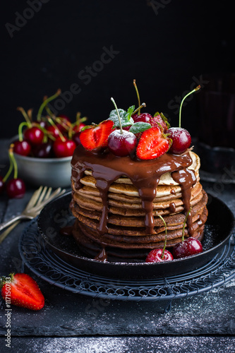 Photo Ombre chocolate pancakes with fresh berries and chocolate sauce