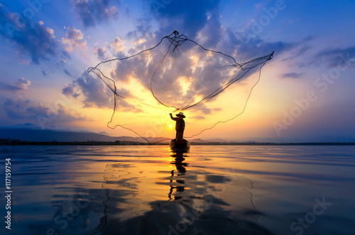 Fotografie, Obraz  Asian fisherman on wooden boat casting a net for catching freshwater fish in nat