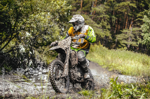 plakat dirty racer motorcycle Enduro riding through a puddle in forest