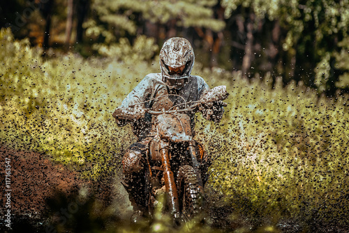 plakat extreme motocross competition: athlete racer goes through a puddle of mud