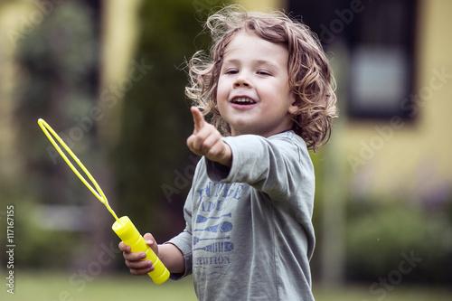 Kleiner fröhlicher junge mit Seifenblasen Canvas Print
