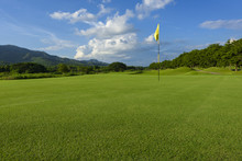 Golf Course And Yellow Flag,green Fields And Blue Sky