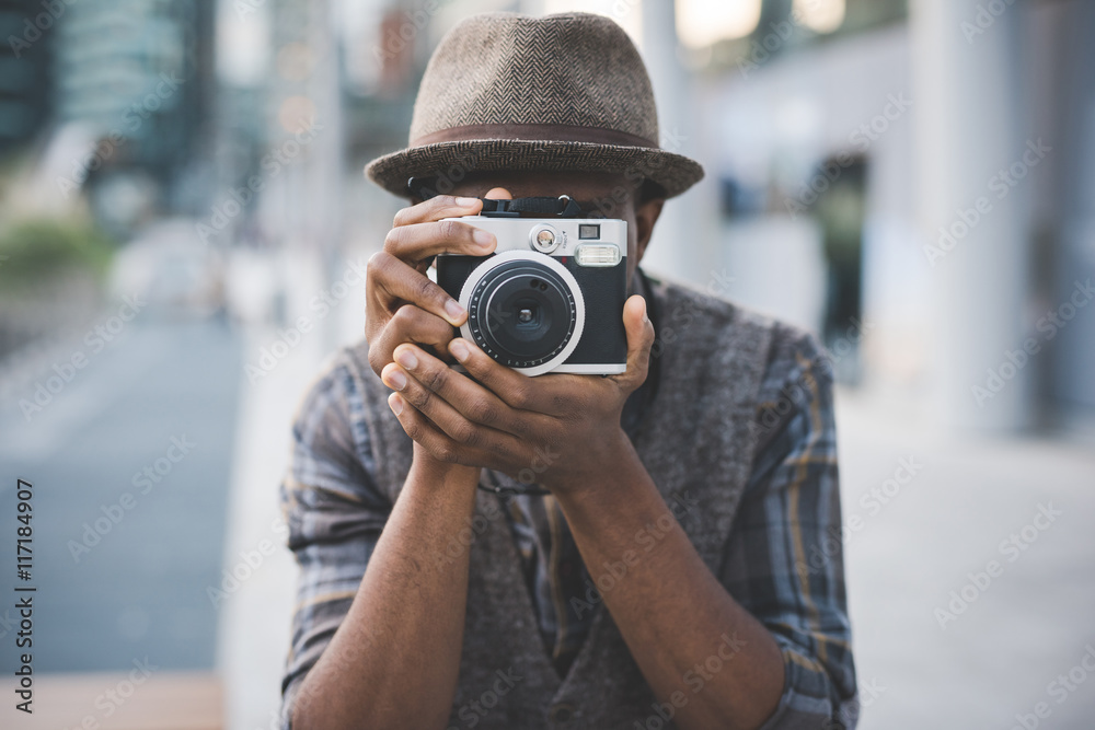 Fototapeta Half length of young beautiful afro black man outdoor in the city holding instant camera, shooting - photography, creative, artist concept
