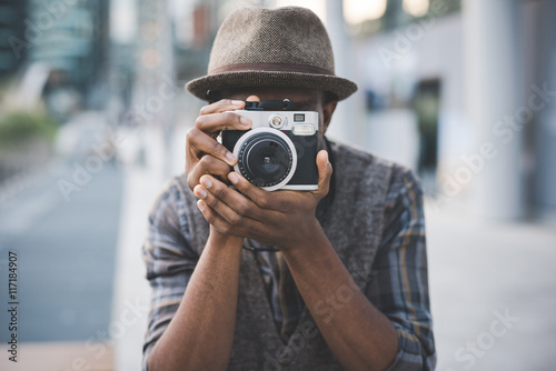 Half length of young beautiful afro black man outdoor in the city holding instan Fototapet