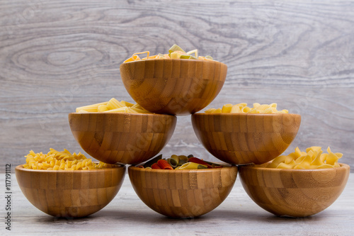 Canvas Prints Spices Various combinations of pasta on wooden background, burlap bags, bamboo bowls. diet and nutritional concept.