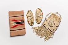 Authentic Native American Made Baby Slippers And Hand Bags On A Light Background