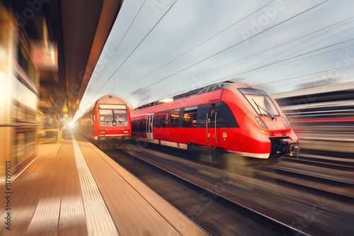 Foto  Modern high speed red passenger trains at sunset