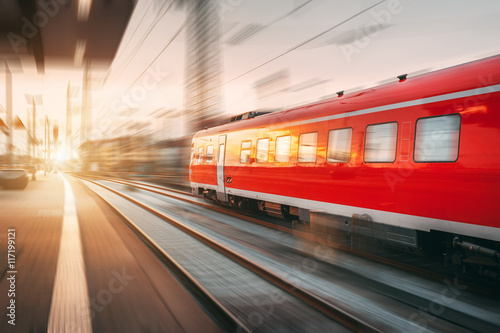 Vászonkép  Modern high speed red passenger train moving through railway station in the evening