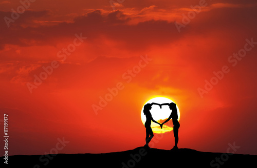 Foto op Canvas Baksteen Landscape with silhouette of young sporty women holding hands in heart shape on the background of sun at sunset in summer. Happy girls
