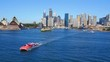 Aerial footage of Red Rocket Ferry at Sydney Opera House in Sydney Harbour, featuring Sydney CBD, Sydney Sky Line, City, Sydney Opera House, Sydney Ferries (ferry), Circular Quay, Parramatta River.