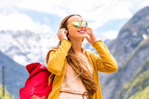 Photo sur Toile Magasin de musique Young female tourist listening to the music in the mountains. Traveling in Triglav national park in Slovenia