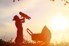 Silhouette Of Mother With Little Baby And Stroller At Sky
