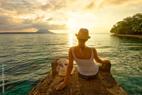 Fotografie, Obraz  woman backpacker sitting on pier and enjoying sunset