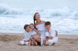 Portrait of cheerful, happy mother and sons on beach