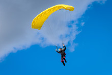 Skydiver In The Air Under The Yellow Canopy