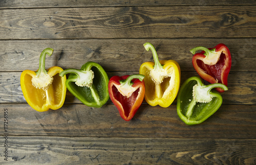 Stampa su Tela Colorful sweet bell pepper halves on a wooden table top background
