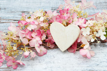 Flower And Wooden Heart Lying On Wood