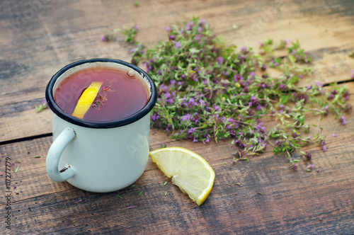 Photo  Tea in an iron mug, lemon, medicinal herbs on a wooden surface.