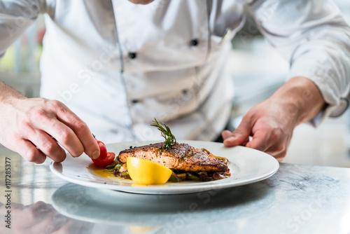 Printed kitchen splashbacks Restaurant Koch mit Sorgfalt beim Garnieren eines Gerichts, Fisch mit Gemüse