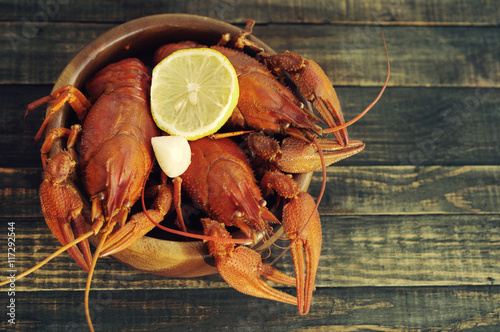 Fotobehang Schaaldieren Boiled crawfishes in a round wooden plate on a wooden background, top view