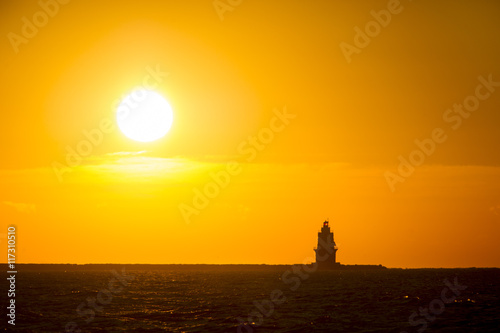 Fotografia, Obraz  The sun rises behind a silhoetted lighthouse in the Atlantic Ocean