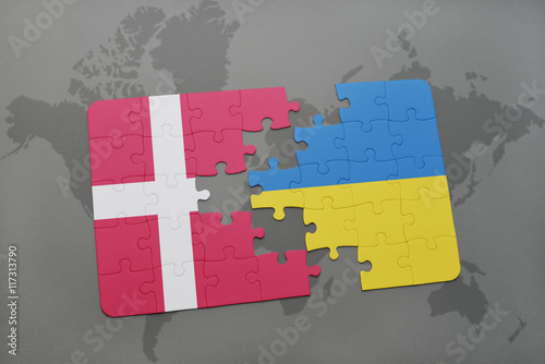 Photo  puzzle with the national flag of denmark and ukraine on a world map background