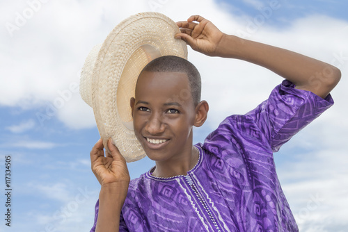 Smiling teenager holding a boater straw hat Wallpaper Mural