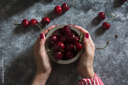 Staande foto Vruchten Woman Holding a Bowl with Fresh Cherries