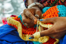 Hands Of Indian Woman Knitting A Mat