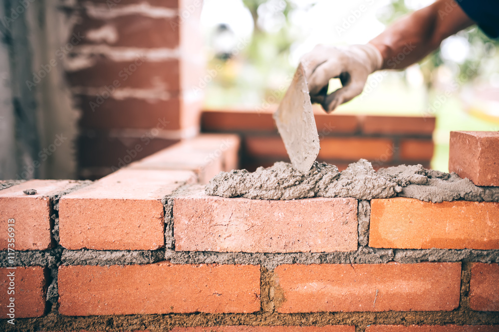 Fototapeta industrial Construction bricklayer worker building walls with bricks, mortar and putty knife.