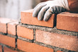 canvas print picture - Close up of industrial bricklayer installing bricks on construction site