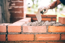 Industrial Construction Bricklayer Worker Building Walls With Bricks, Mortar And Putty Knife.