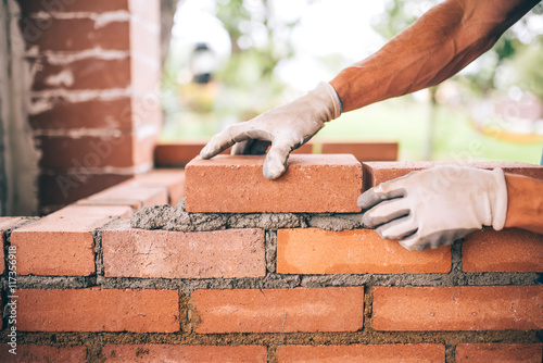 Fotografía  professional construction worker laying bricks and building barbecue in industrial site