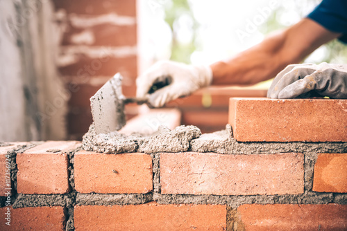 Photo Bricklayer worker installing brick masonry on exterior wall with trowel putty kn