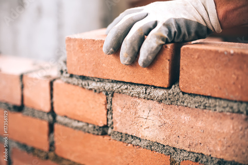 Fotografia Close up of industrial bricklayer installing bricks on construction site