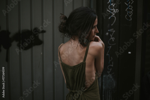 Brunette with hairstyle in khaki dress looking away Poster
