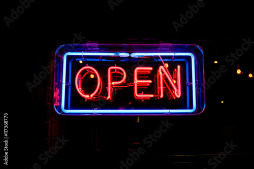 Fotografia  neon OPEN sign welcomes customers